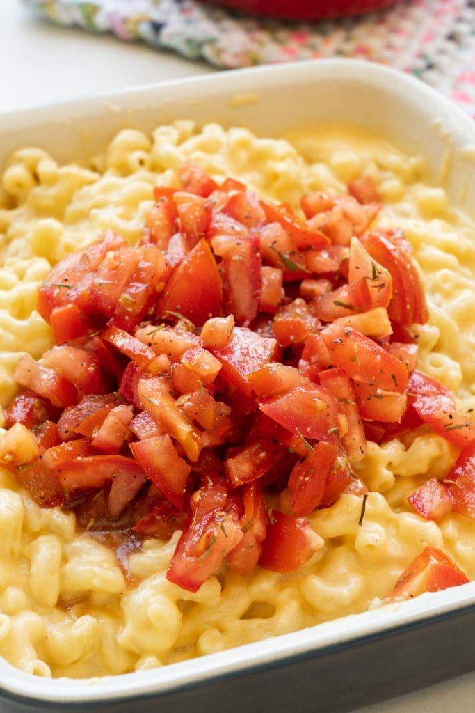 diced tomatoes on top of macaroni and cheese.