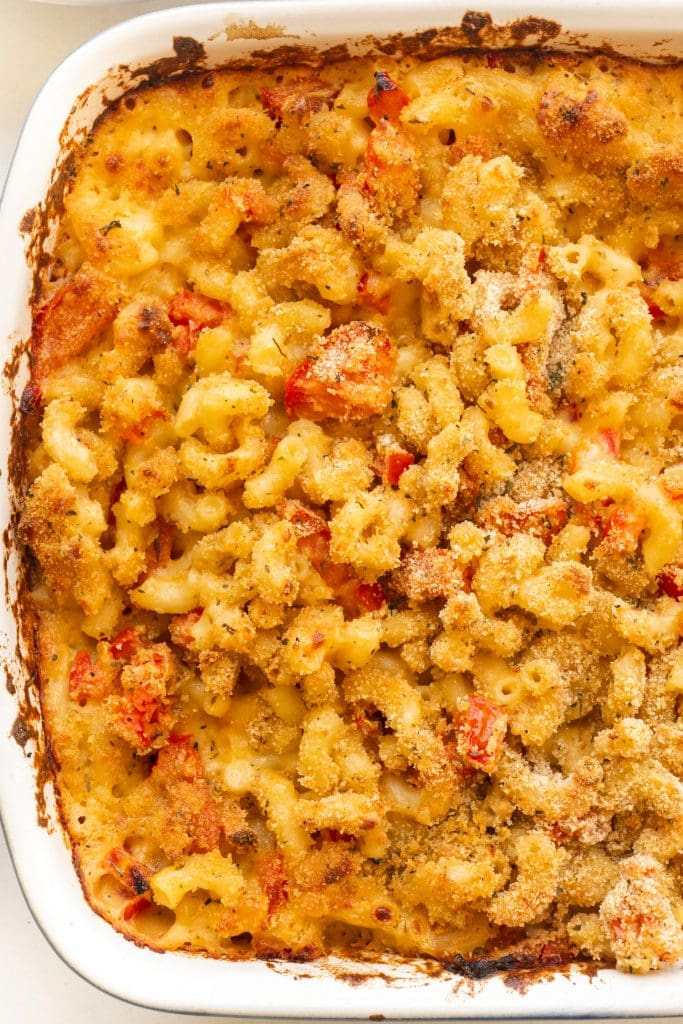 baked macaroni and cheese in baking dish with tomatoes.