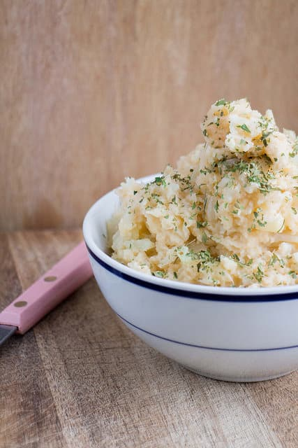 CREAMY Cauliflower Mashed Potatoes, this easy recipe is just like mashed potatoes but doesn't use potatoes or milk! Dish uses cheddar cheese and cream cheese to make them extra creamy! Great for a healthy keto diet!