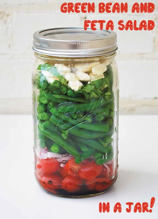 Easy to make Mason Jar Green Bean and Feta Salad. Ingredients for this healthy salad include green beans, tomatoes, shallots, balsamic vinaigrette, feta cheese and basil.