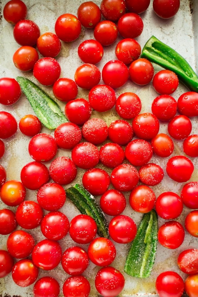 cherry tomatoes with garlic and jalapenosn on baking sheet.