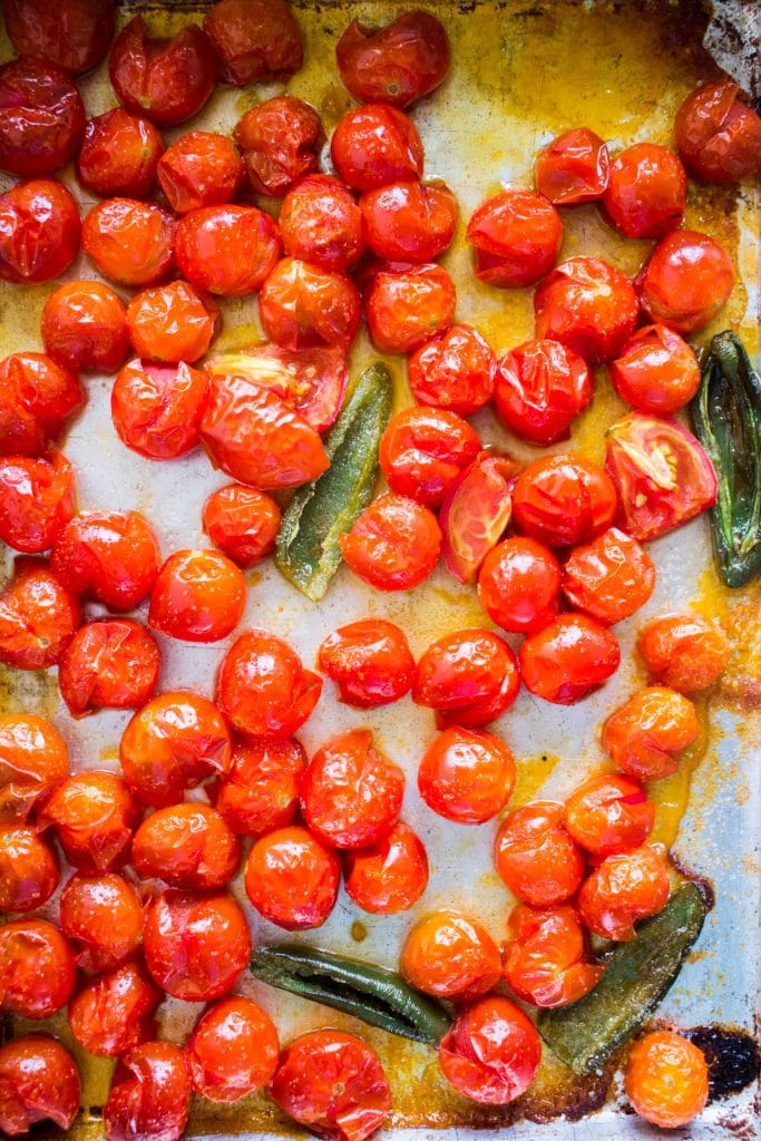 baked tomatoes that are wrinkly and popping on baking sheet.