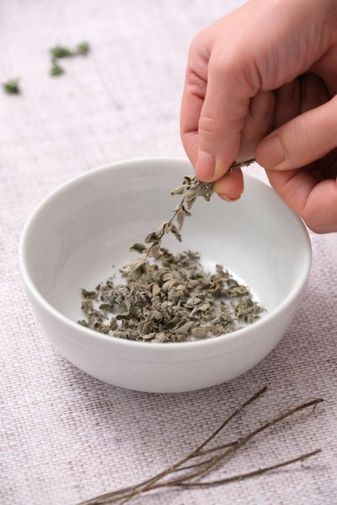 hand crumbling oregano leaves into white bowl