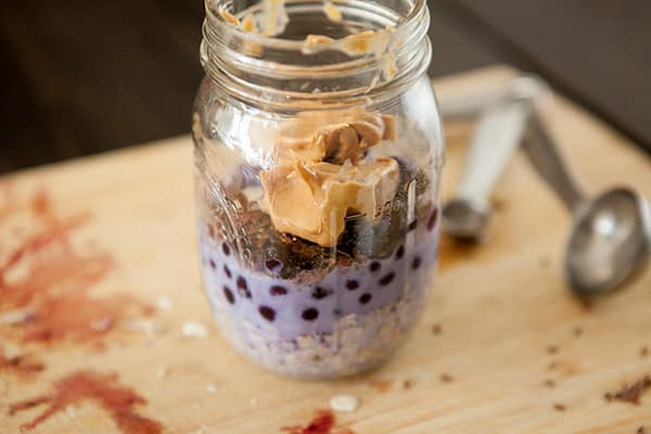 Overnight Blueberry Peanut Butter Oatmeal is a breakfast that's ready for you in the morning. This recipe uses old fashioned oats, creamy peanut butter, flax seeds, maple syrup and blueberries to make it one delicious quick breakfast.