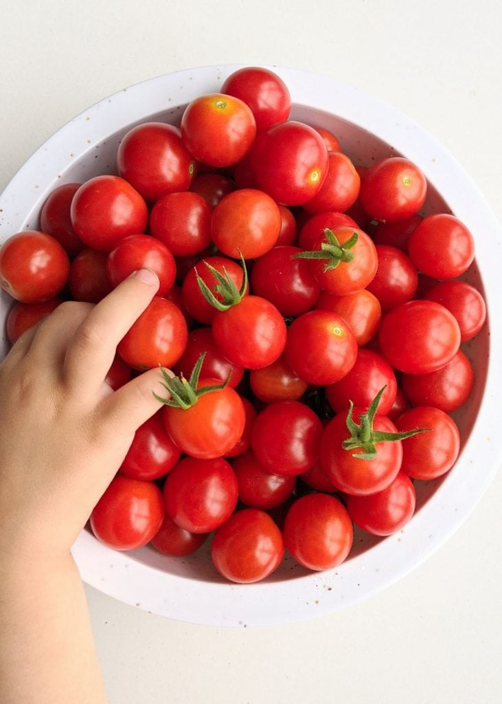 bowl of cherry tomatoes with hand going into it.
