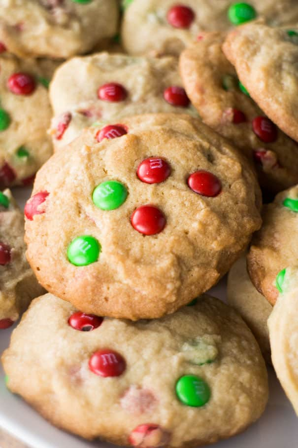 These M&M Christmas Cookies are made with a simple, delicious sugar cookie dough and plenty of chocolate candy pieces. A fun and festive treat for cookie exchanges and gift giving that can easily be customized to suit your occasion!