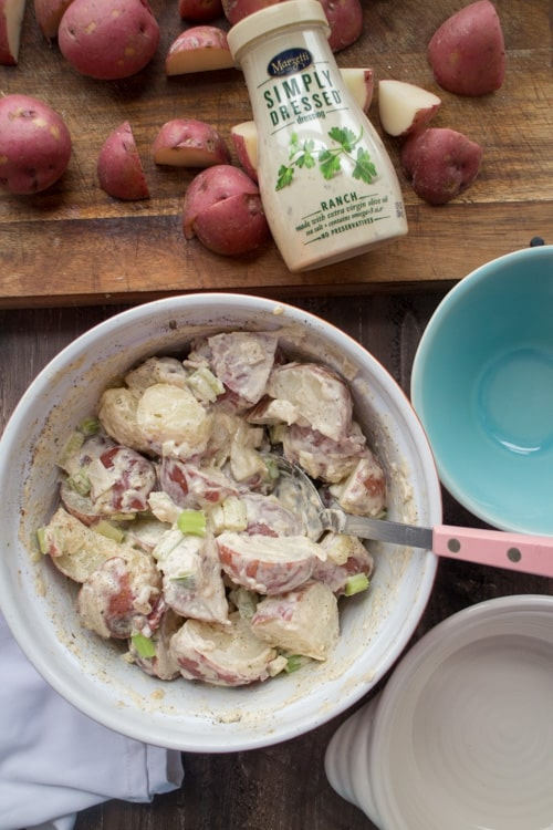 CREAMY Ranch Potato Salad that doesn't require potato peeling!  This loaded, easy to make potato salad recipe has the classic taste you grew up with and is ready in 20 minutes! It's made with ranch dressing (no mayo!) to make it extra creamy! Enjoy this warm in the Winter or chilled in the Summer!  It's a must have your next grilling session!