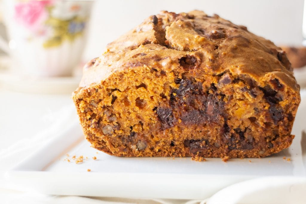 loaf of chocolate chip carrot bread with exposed slice on white plate.