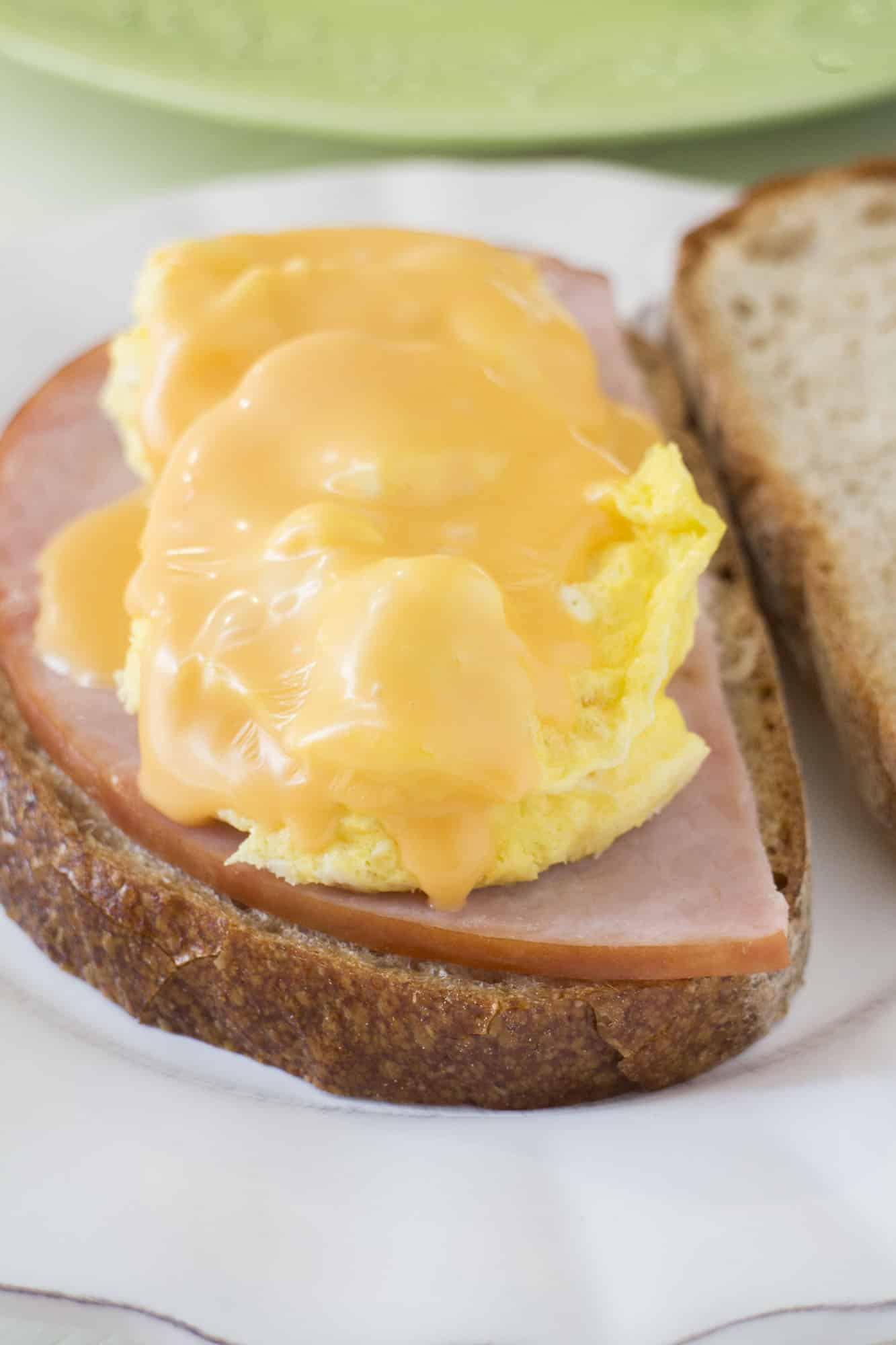 EASY, YUMMY breakfast sandwich made in 2 MINUTES! This Maple Syrup, Egg, Ham and Cheese Sandwich recipe is great for a quick breakfast! You can freeze the sandwiches to make ahead too! They taste like french toast to me!