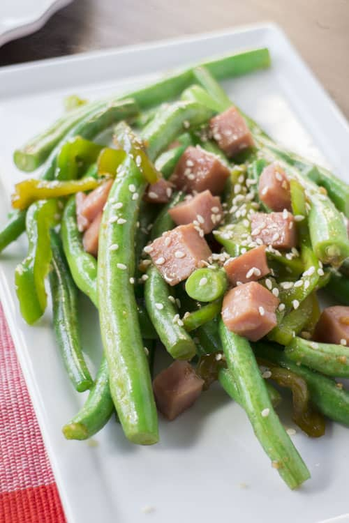 asian green beans with ham on top on white plate