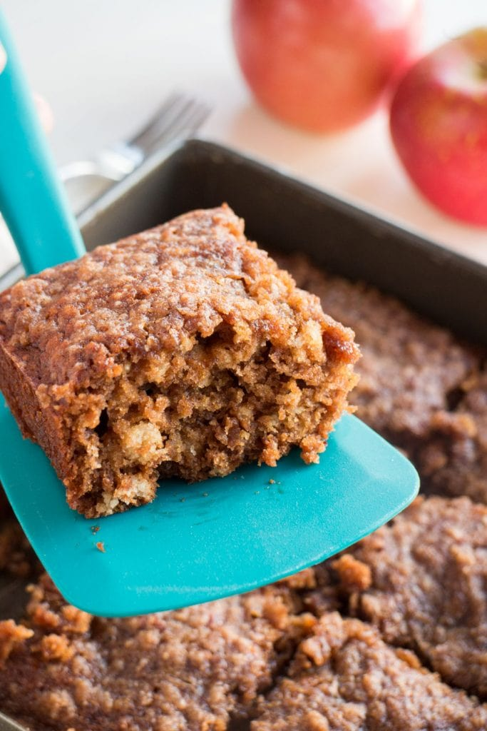 one apple brownie being lifted out of pan on blue spatula