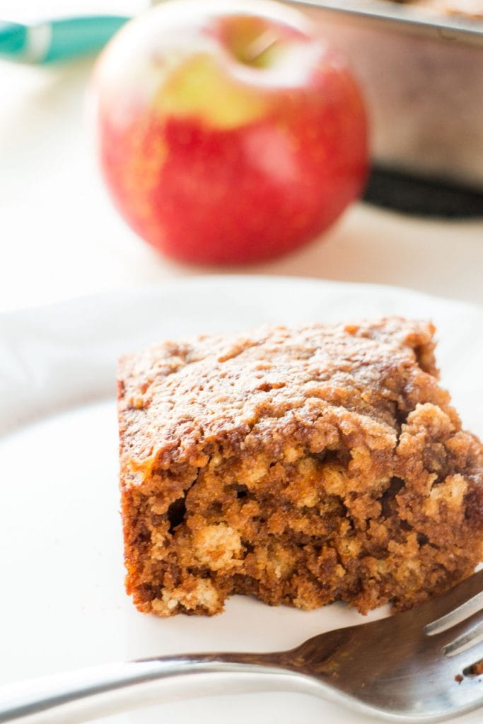 applesauce brownie on white plate with fork with red apple behind it