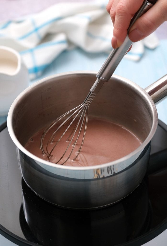 whisk mixing almond milk and protein powder