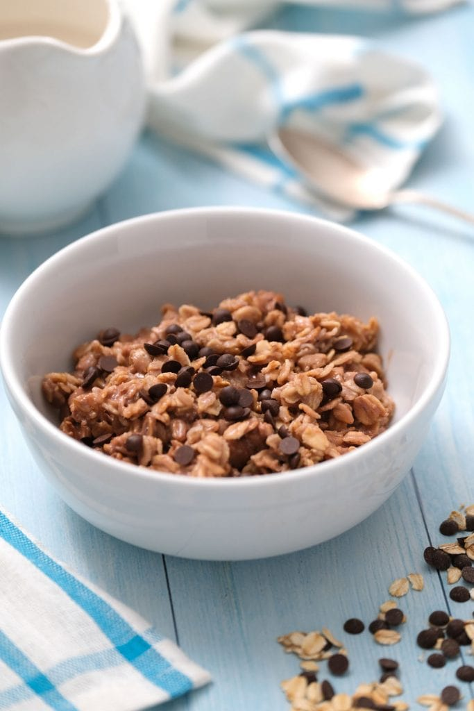 bowl filled with chocolate protein powder oatmeal with chocolate chips on blue table