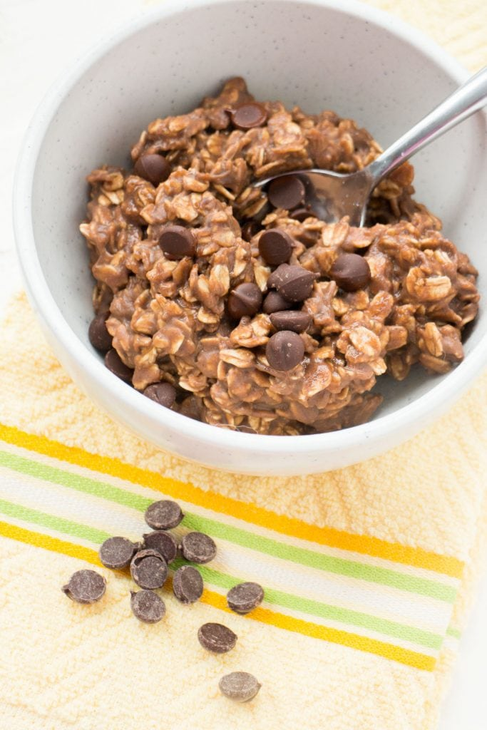 chocolate protein powder oatmeal in white bowl with chocolate chips, spoon going in