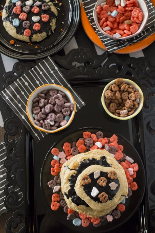 Spooky Halloween Frosted Pancakes with Count Chocula, Boo Berry and Franken Berry Cereal on top. They're perfect for a fun holiday breakfast!