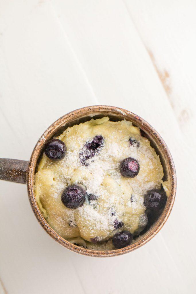baked blueberry mug cake on white wooden background