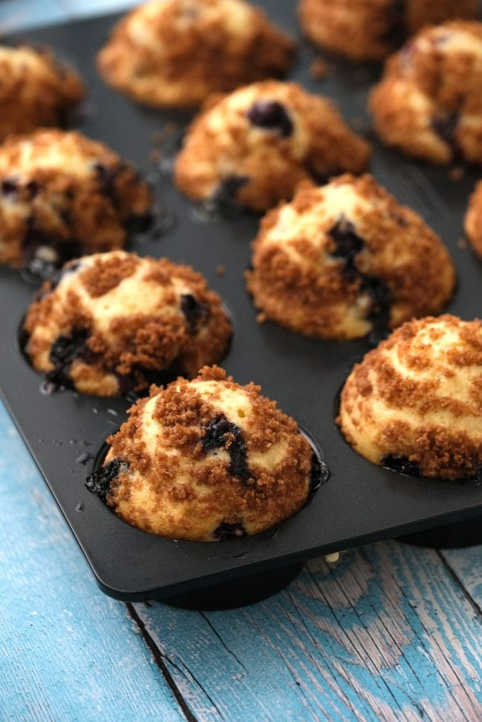 mini blueberry muffins in pan with streusel topping