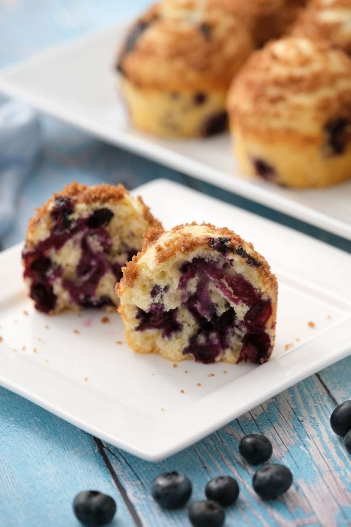 mini blueberry muffin with lots of blueberries inside, on white plate
