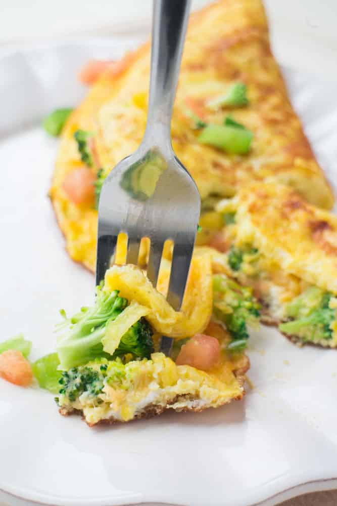 Cheesy Vegetable Omelette is packed with garden fresh vegetables! This breakfast recipe is easy to make and shows you how to make a perfect cheesy omelette step by step! The best part is that you can customize it what veggies you have - my favorite are tomatoes, broccoli and peppers to add in!