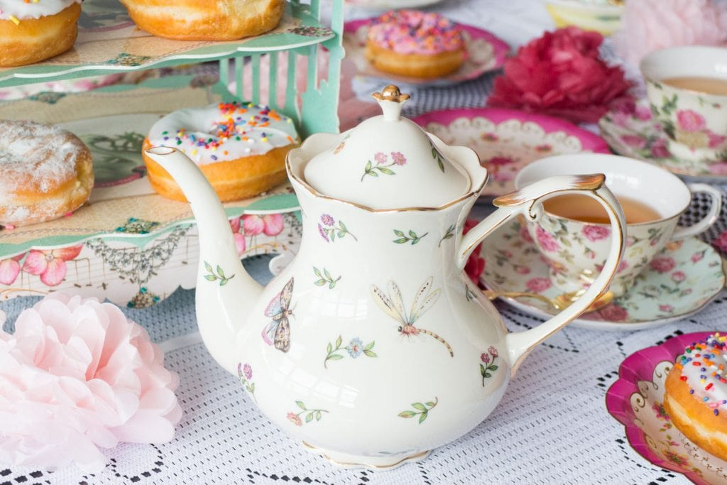 floral tea kettle on lace table cloth