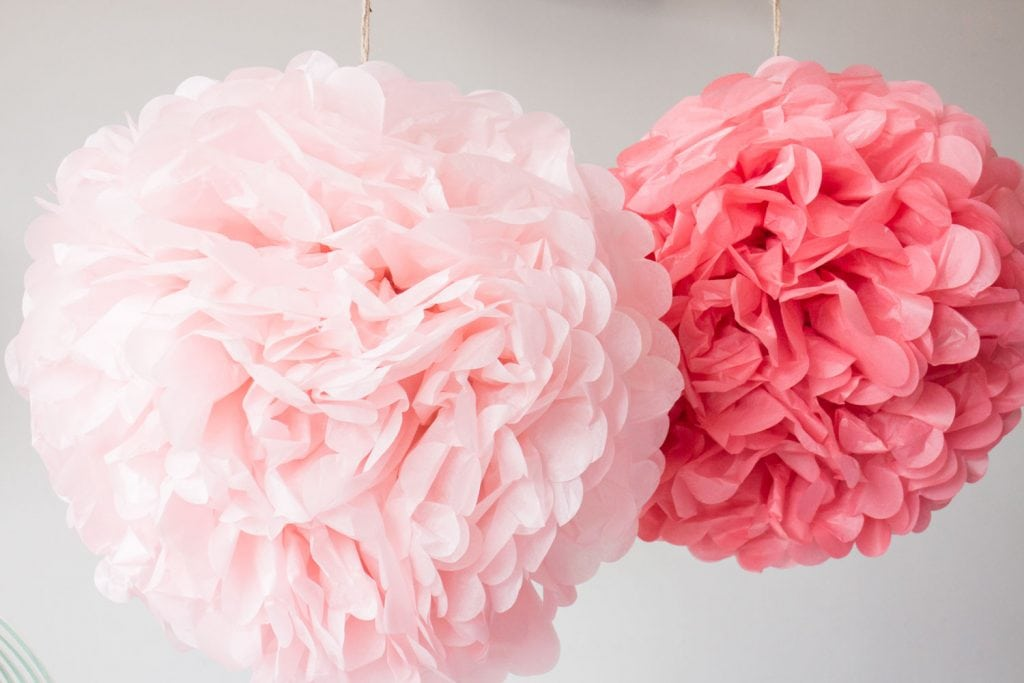 pink pom poms hanging from ceiling