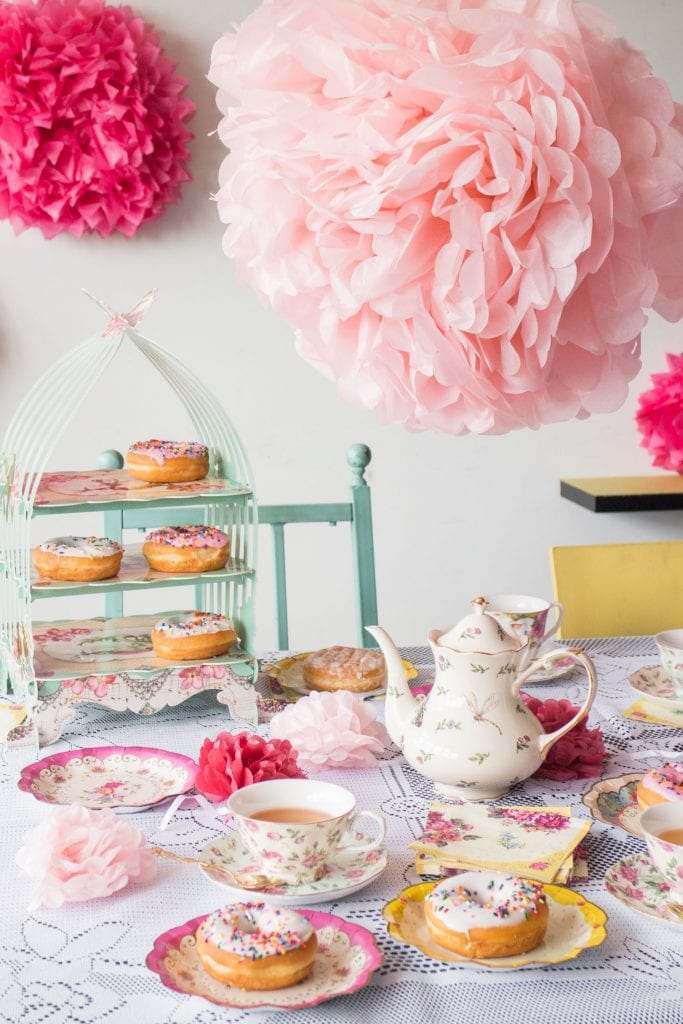 donuts, tea cups and plates on table for tea party