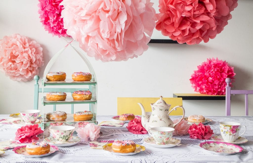tea party set up on table with food and tea kettle, tea cups