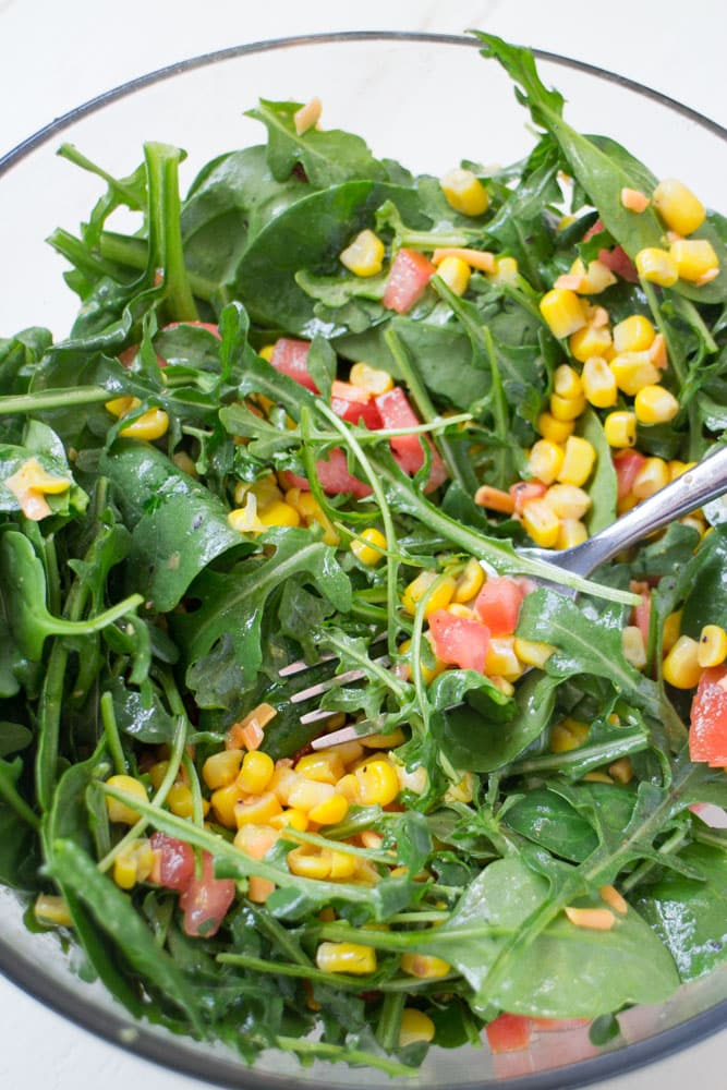 EASY Mexican Arugula Corn Salad with Lime Olive Oil dressing!  This simple, healthy salad recipe includes Arugula, Spinach, Tomatoes, Corn and a Olive Oil/Lime/Cumin dressing to give it a Mexican taste! This is a perfect side salad but could easily turn into a main course if you add chicken to it.  My family loves this salad, it makes healthy eating easy!