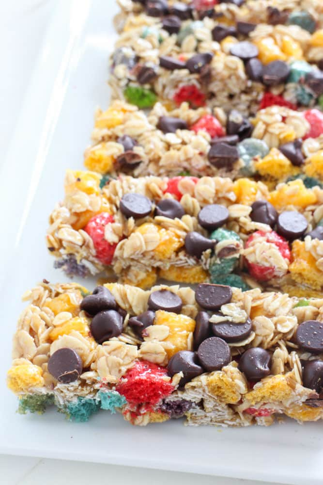 RAINBOW Crunch Granola Bars made with chocolate chips! This homemade no bake recipe makes crunchy granola bars made with oatmeal and rainbow cereal! Kids love making them alongside Mom for breakfast and lunch treats!