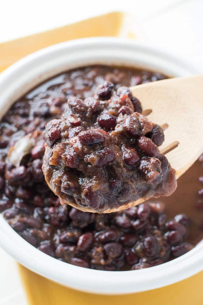 EASY SLOW COOKER black beans made with dried beans! This healthy, vegetarian recipe cooked in the crock pot for 4 hours is so easy and healthy! Because it uses dried beans it's cheap to make too! We love serving these beans on flour tortillas for black bean tacos! It's one of my families favorite comfort foods!