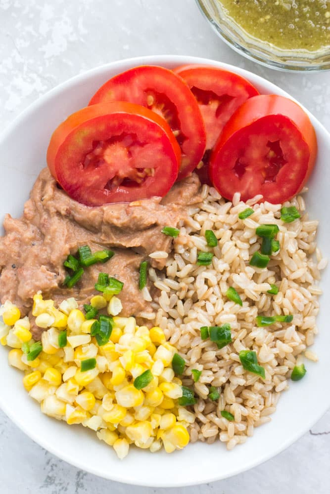 Vegetarian Mexican Burrito Bowl that includes rice, refried beans, corn, tomato, pepper and salsa. Perfect for work lunches or quick dinners as it only takes 5 minutes to make!