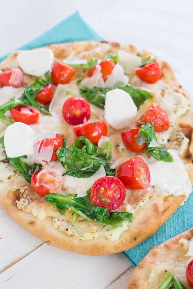 Delicious Truffled Three Cheese Flatbread with grape tomatoes and arugula! Ready in under 15 minutes! Only 650 calories per serving!