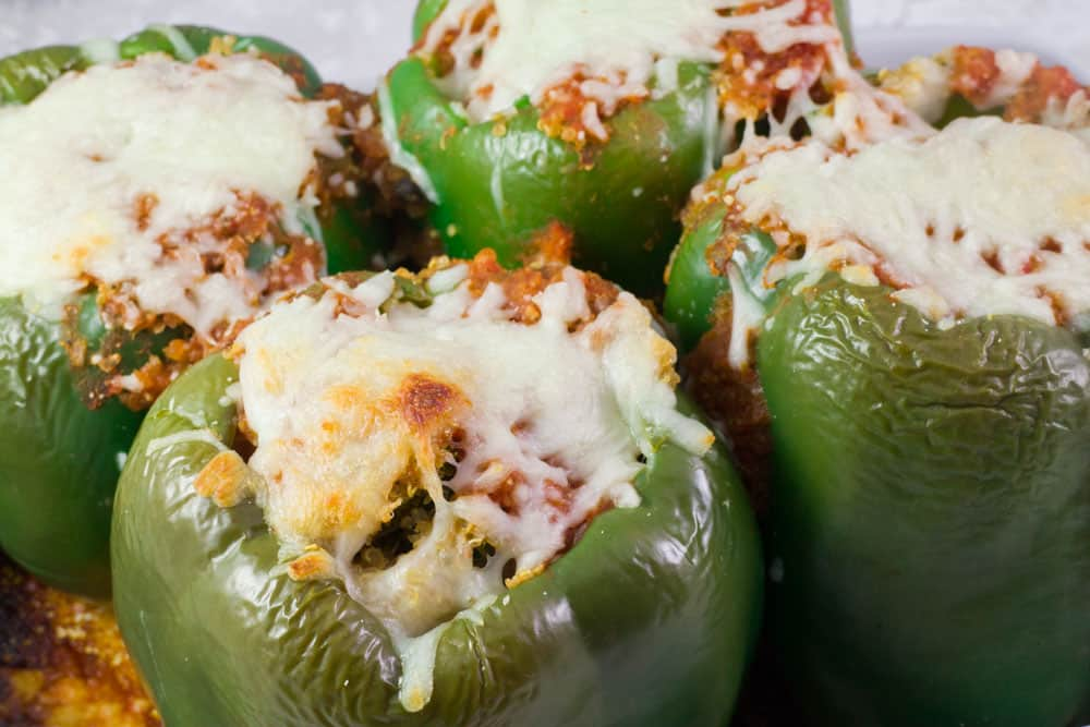 Delicious Stuffed Green Peppers recipe that is smothered in cheese and stuffed with Quinoa and Kale inside. Enjoy this comforting healthy meal for dinner soon!