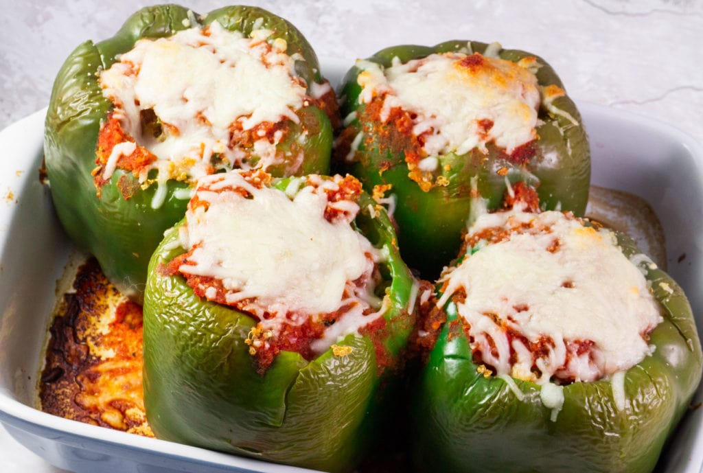 Vegetarian Stuffed Peppers recipe recipe made with quinoa, kale and covered in cheese!  This easy healthy recipe is perfect to add to your meatless dinner menu! Vegan option offered.