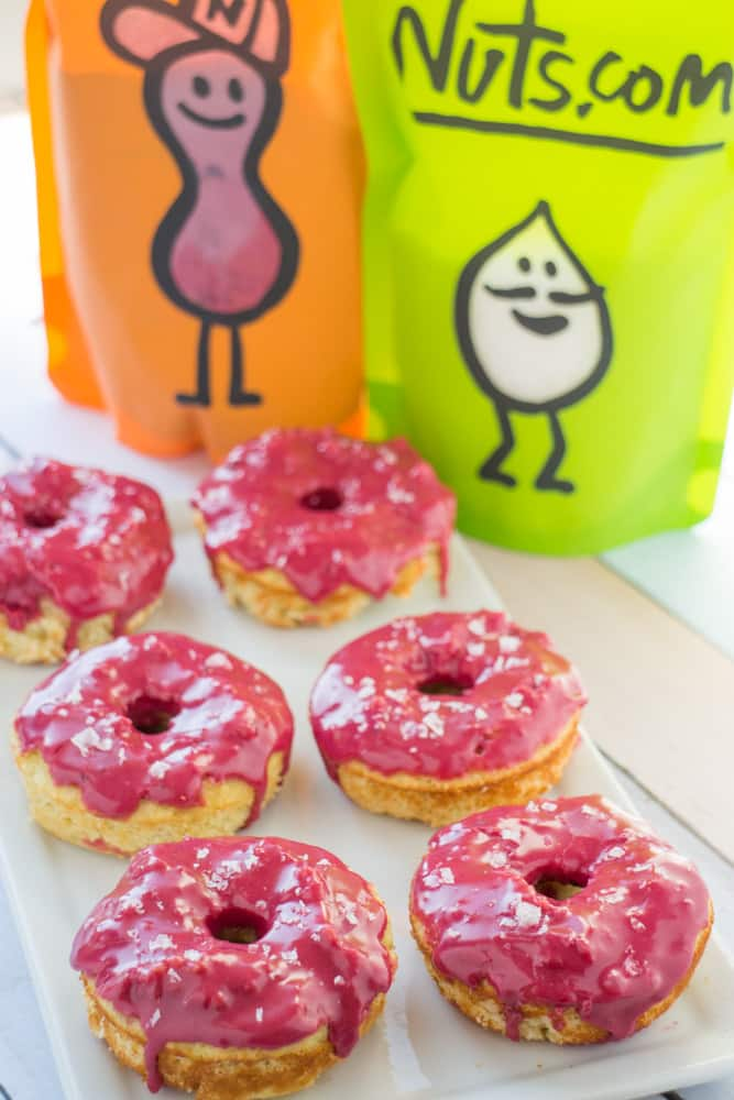 These donuts are so pretty and yummy! Gluten Free Baked Vanilla Donuts recipe with a bright pink frosting on top! The icing glaze is completely all natural and made with beet powder - which has no beet taste to it! These cute donuts are great for birthday party, bridal party and wedding desserts!