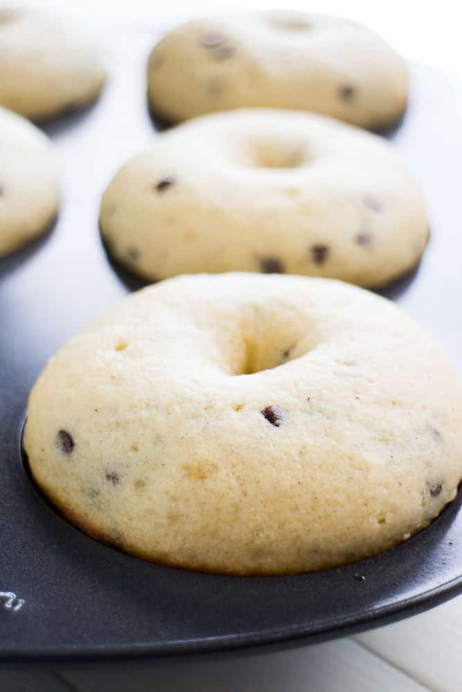 BAKED Chocolate Chip Chocolate Frosted Donuts are AMAZING! This easy recipe makes fluffy delicious homemade donuts that are ready in 10 minutes! Mini chocolate chips are baked inside the donuts with the best chocolate frosting on top! I'm in love with these double chocolate donuts!