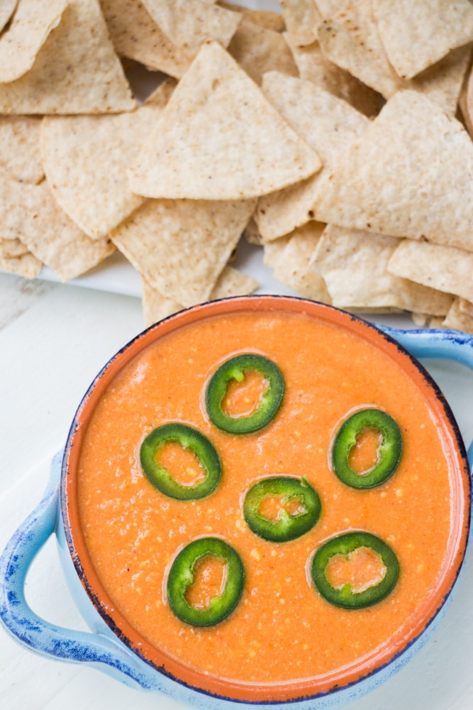 Slow Cooker Tomato Cheese Dip is a creamy easy to make dip that uses fresh tomatoes, peppers and Velveeta cheese! This simple homemade recipe is ready in 2 hours in the slow cooker and perfect to serve with tortilla chips for your next party! We especially love this dip for Mexican meals!