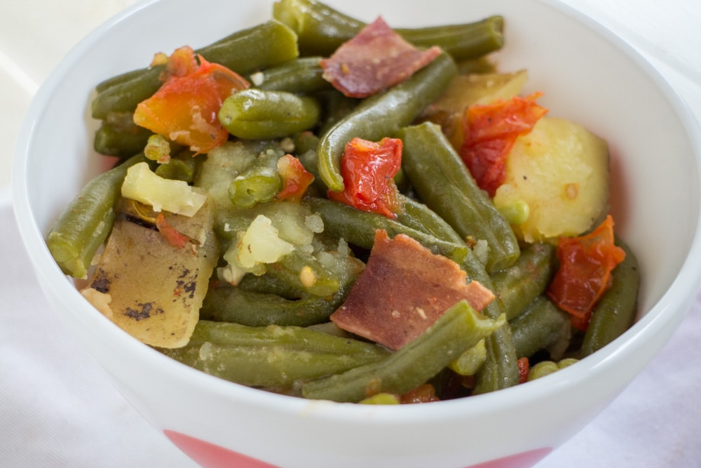 SLOW COOKER Green Beans and Tomatoes! This easy recipe cooks fresh green beans, tomatoes, potatoes and bacon in a crock pot for 4 hours. This is a healthy dish that you can serve over rice or as a side dish to chicken or Thanksgiving holiday dinners. This has been become one of families favorite meals!