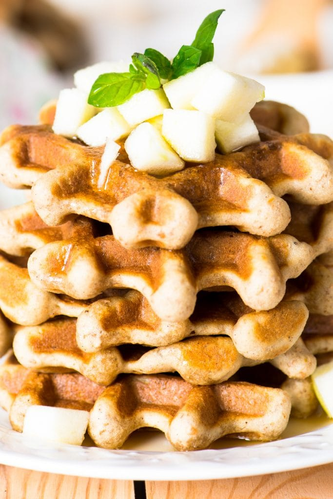 stack of apple waffles with syrup and diced apples on top.