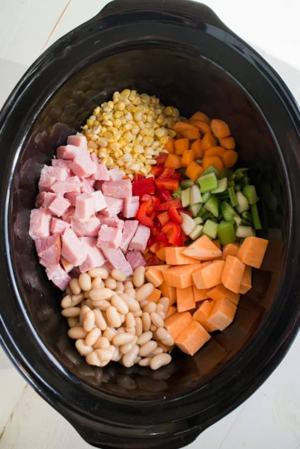 CREAMY SLOW COOKER Sweet Potato Soup recipe! This easy Crock Pot soup includes ham, sweet potatoes, celery, carrots, red pepper, onion, corn and white beans in a cheesy broth! It's a great idea for leftover ham for dinner and it's packed with healthy vegetables!