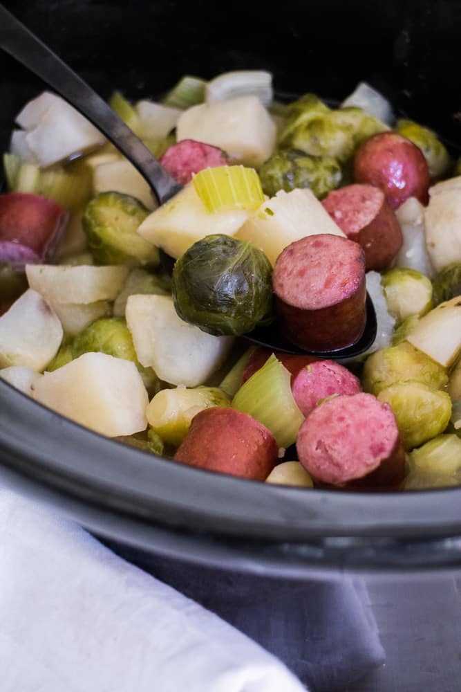 FAMILY FAVORITE Slow Cooker Kielbasa, Brussels Sprouts and Potatoes! This healthy dinner is so easy to make as it only takes 5 hours in the crock pot! The meal cooks in a beef broth brown sugar mix that is amazing! It's one of my family's favorite comfort food recipes for a Winter night! We love serving it over egg noodles or rice!