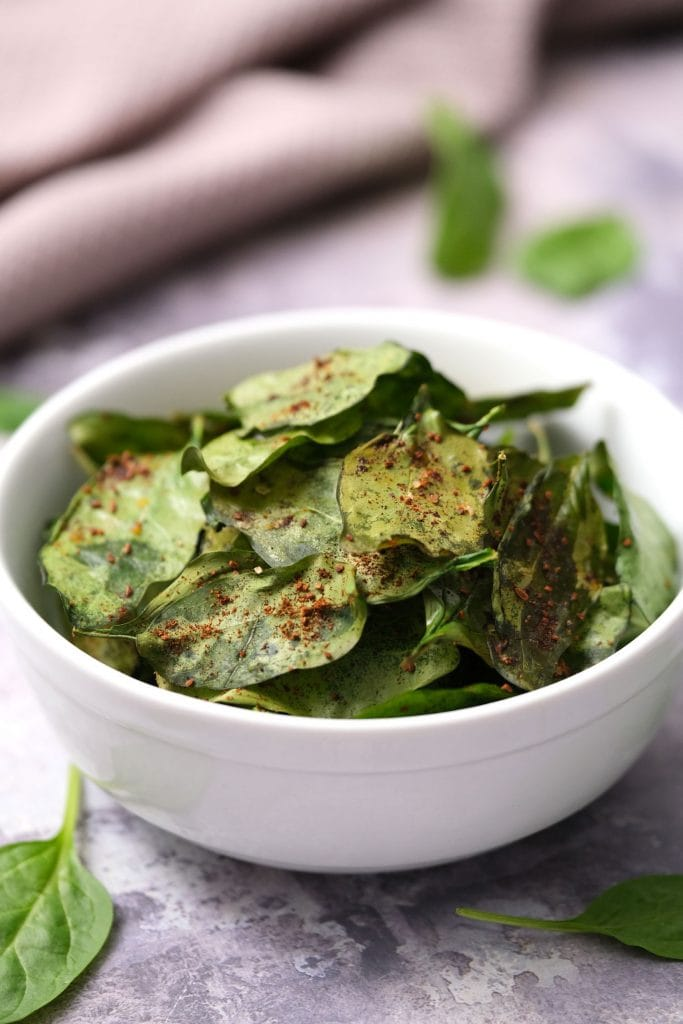bowl of baked spinach chips on table