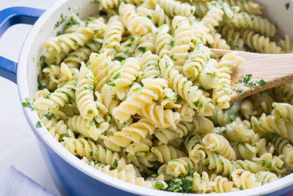 Parsley Parmesan Pasta recipe that takes 15 minutes to make and costs less than $4.   Blend the parsley with other simple ingredients to make a nut free pesto sauce and then pour on top of pasta! Your entire family will like this fresh parsley pasta dinner.