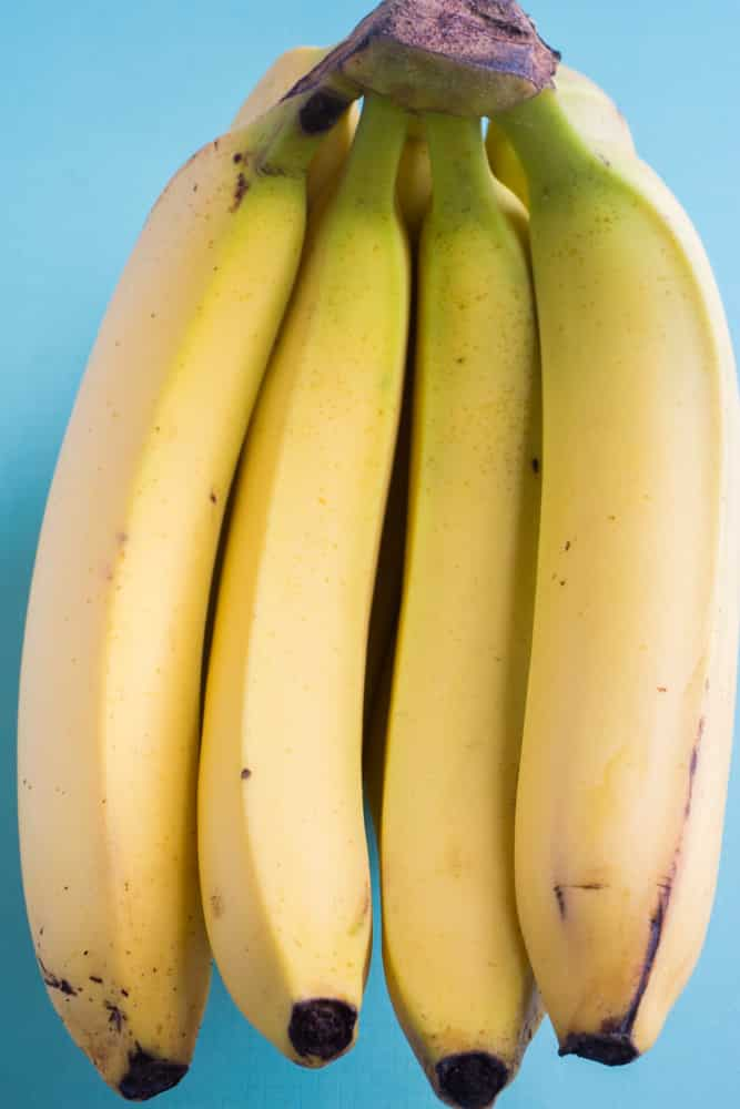 How to Store Bananas!  These easy tips will prevent your bananas from turning brown!  Tricks includes storing with other fruit, plastic wrap, banana trees and how to freeze bananas!  Learn the best ways to store bananas and keep them green for longer!