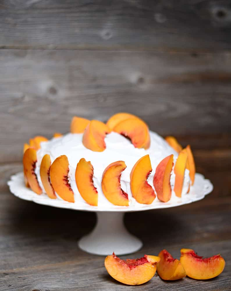 EASY to make Peach Cake with Vanilla Frosting recipe. The cake is so moist and made with fresh peaches inside and for decoration on top. This cake is made with two 8 inch cake pans layered together.  It's the perfect cake for Summer peach season!
