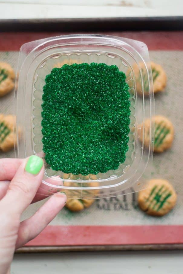 hand holding package of green sprinkles