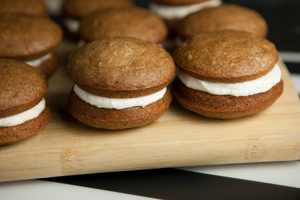 These incredible pumpkin whoopie pies are made with two soft and fluffy pumpkin cake-like cookies and a layer of marshmallow filling sandwiched in between. It's a fun and perfect little treat you can eat right out of your hands.