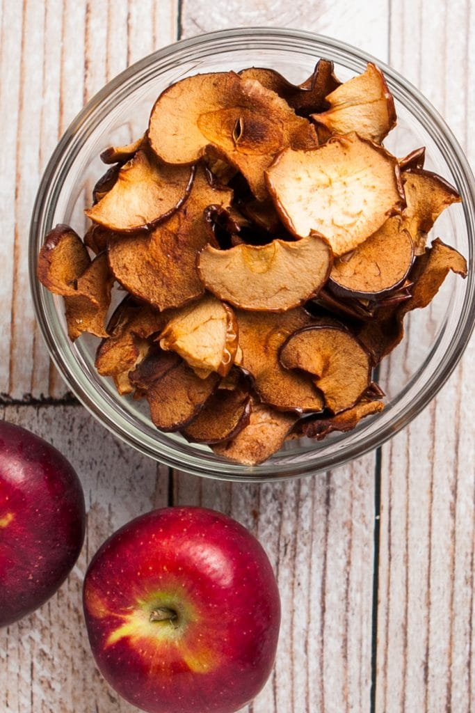 glass bowl filled with baked apple chips.