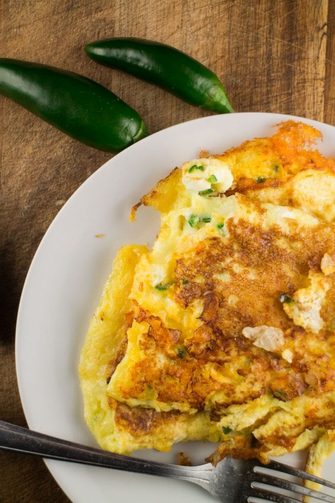 cheesy omelet on white plate with jalapeno peppers next to it